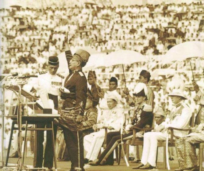 """LE PREMIER MINISTRE TUANKU ABDUL RAHMAN (1903 + 1990) CRIE 7 FOIS """"PERMEKA""""  - LIBERTE ou INDEPENDANCE - REPRIS EN CHOEUR PAR LE STADE ARCHI-COMBLE  . ENSUITE RETENTIT L'HYMNE NATIONAL  """"NEGARAKU"""""""