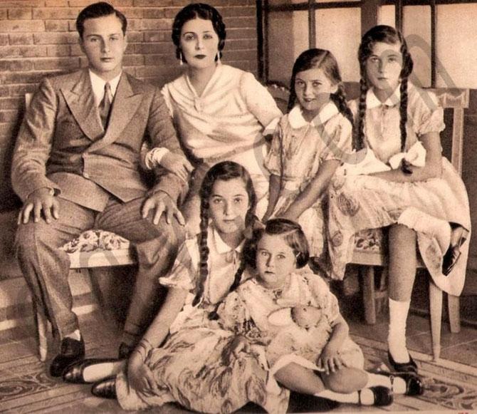 1936. g. à dte. LE ROI FAROUK, LA REINE NAZLI, LES PRINCESSES FAIKA ET FAIZA. Assises par terre LES PRINCESSE FAWZIA et FATHIA AVEC SON OURSON EN PELUCHE.