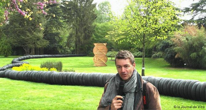 """MAI 2014 CHÂTEAUBOURG LE JARDIN DES ARTS (PARC AR MILIN). JERÔME LEYRE, DIPLÔME DES BEAUX-ARTS DE CLERMONT-FERRAND DEVANT SA SCULPTURE SPIRALE EN PIN NATUREL. JUSTE DERRIERE LUI LE """"SERPENT"""" EN CAOUTCHOUC DU RENNAIS ERIC DEROOST : UNE PUB POUR BIBENDUM ?"""