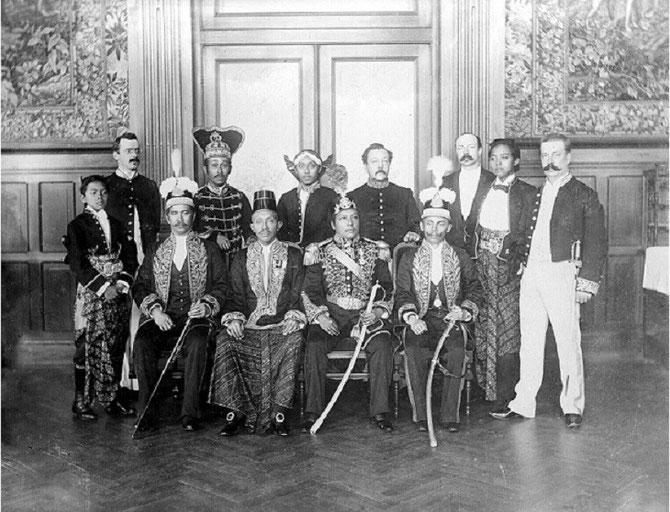 ATTENDANT LE COURONNEMENT, le PRINCE HERITIER DU KUTAI (assis à l'extrême gauche), avec les autres PRINCES INDONESIENS ET OFFICIELS NEERLANDAIS.
