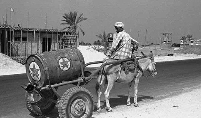 1960 . JUMEIRAH BEACH ROAD. UN BIDON DE CALTEX TIRE PAR UN ÂNON. C*ANITA VAN DER KROL