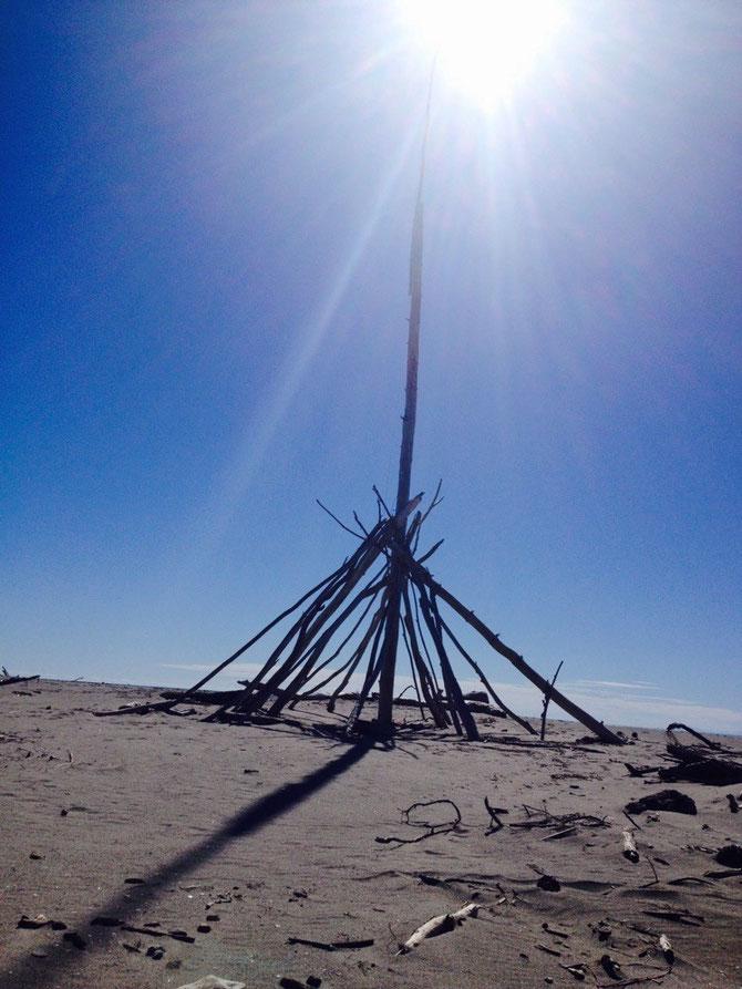 Figur aus Treibholz am verlassenen Strand