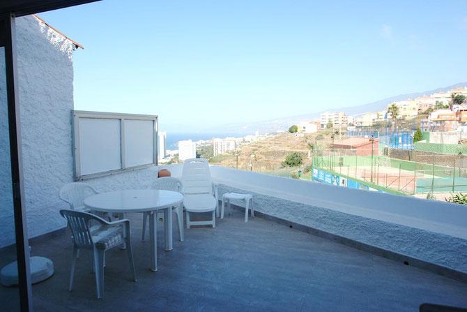 Blick von der Terrasse der Wohnung auf einen Tennisplatz und dem Meer.
