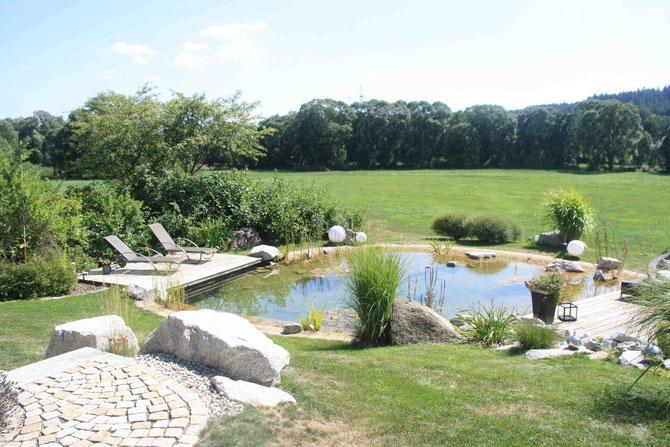 Hausgartengestaltung unter Einbeziehung der angrenzenden freien Landschaft. Optische Erweiterung und eine naturnahe Gestaltung, angepasst an die Umgebung. Ein Schwimmteich lädt zum Baden ein. Urlaubsfeeling pur!