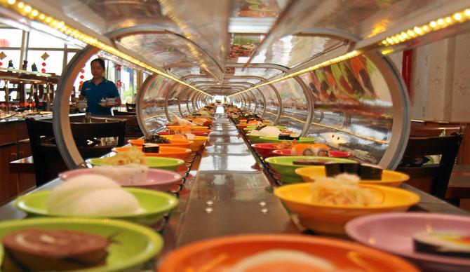 Running Sushi - kleine Teller mit asiatischen Spezialitäten rollen an Ihrem Tisch vorbei