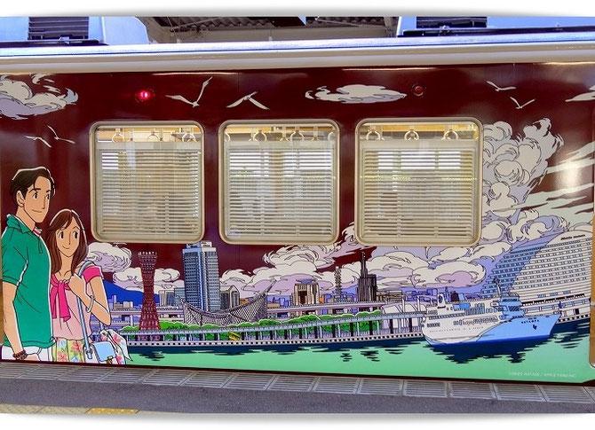 阪急神戸線のラッピング列車。わたせせいぞうさんのイラストで神戸港とポートタワーの風景が描かれた車両です。