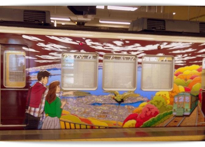 阪急神戸線のラッピング列車。わたせせいぞうさんのイラストで六甲ケーブルと六甲山の天覧台風景が描かれた車両です。