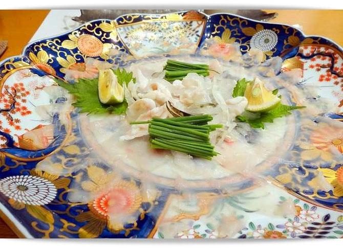 大分市内で食べたフグ料理。写真はお皿の柄が透けて見えるように薄く引かれたてっさの美しい盛り付けです。