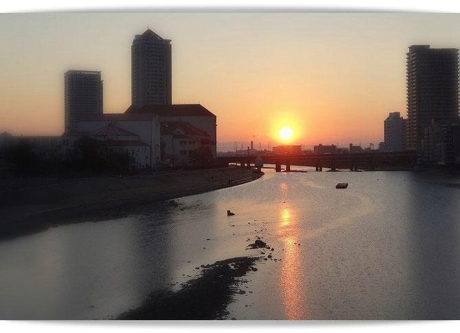 宝塚市蓬莱橋からの初日の出。日の光に宝塚大劇場がうっすらと浮かび上がっています。