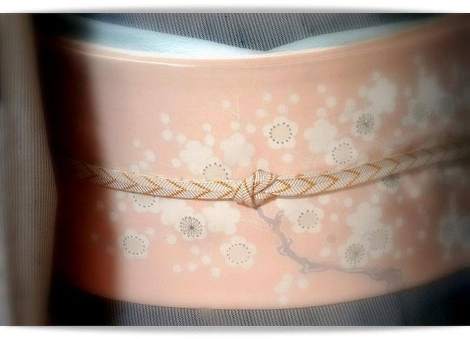 グレー縦縞の伊兵衛織に、新春らしいピンク地に白梅の染め帯。