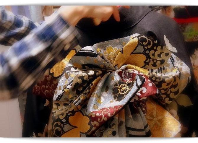 森田空美流着付け教室の初稽古風景。成人式に向けて帯結びを練習しています。写真の帯は「天津風」