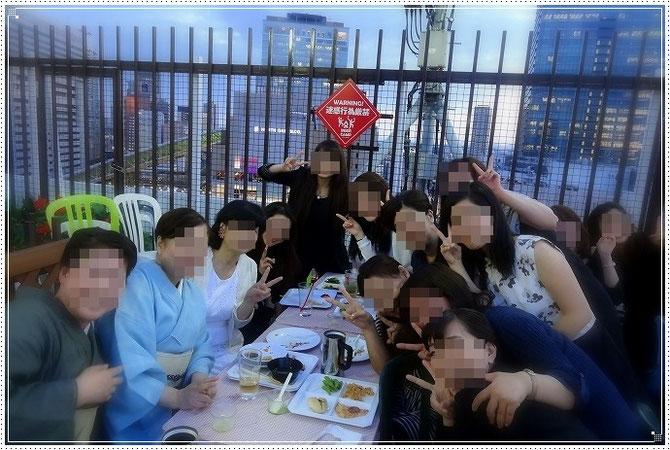 はいチーズ。全員そろっての記念写真。まわりには梅田界隈のビルが見渡せます。