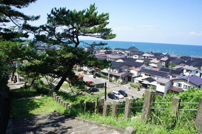 海と山に囲まれながら、互いに肩を寄せ合う名立の街並み。子どもの頃、冬になると、手前の神社の階段でスキー遊びをしていました