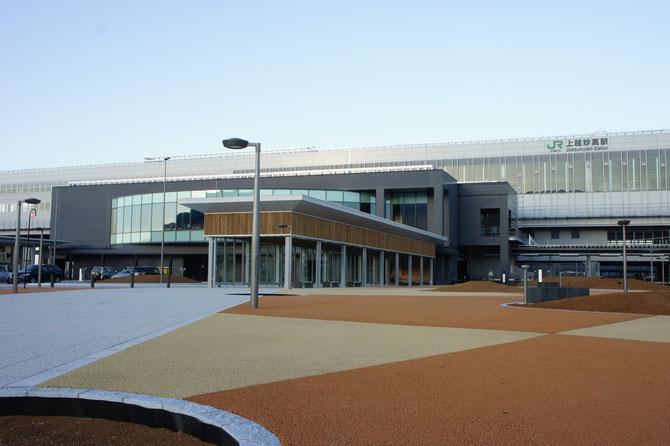 西口から駅舎を望む。白とグレーと木目のコントラスト。都会的でありながらも、なぜか高田城の三重櫓を連想させます