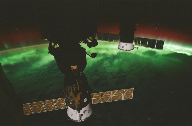 Two Sojus spacecrafts docked on ISS with polarlighteffects in the background over the horizon of earth