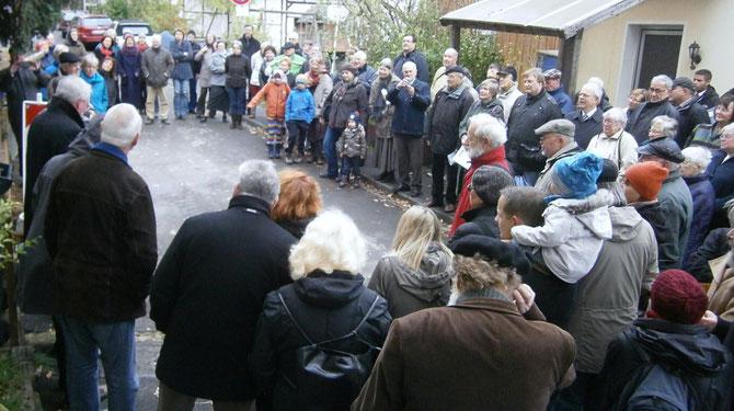 Die Gäste der Steinverlegung bilden einen großen Kreis um die Verlegestelle, in der Mitte schaut der kleine 5-jährige Justus, gleicnamiger Urenkel des Justus Pötter, auf das Geschehen