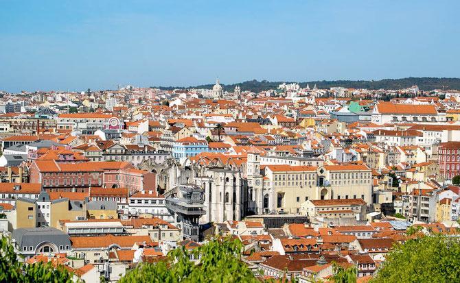 """Blick auf die Stadtviertel Baixa und Bairro Alto. Mit der Basilica de Estrela im Hintergrund und dem berühmten Aufzug """"Elevador de Santa Justa"""" im Vordergrund."""