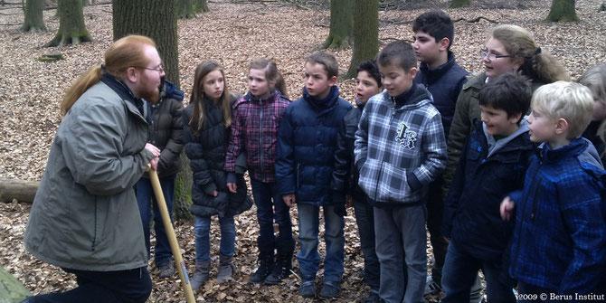 Patrick Urban führt Grundschüler in die Schichten des Waldbodens ein.