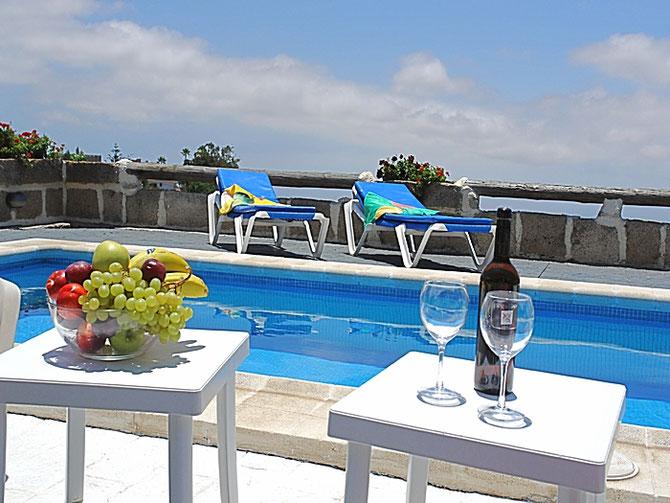 Pool mit gemütlichen Liegen und einer Obstschale sowie ein Flaschen Wein aus Teneriffa.