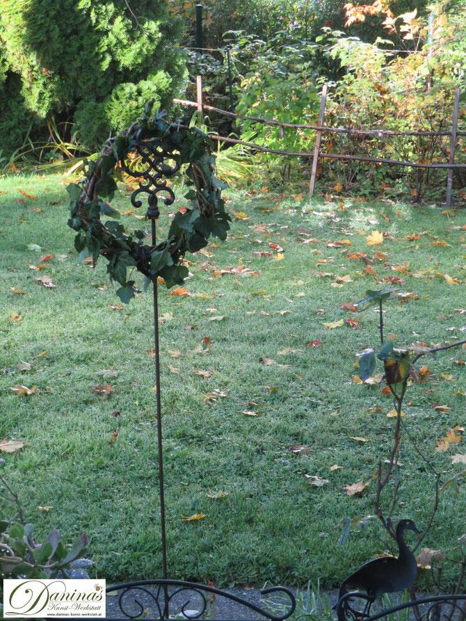 Selbstgebundener Rebenkranz mit Efeu am frostigen Morgen im Garten