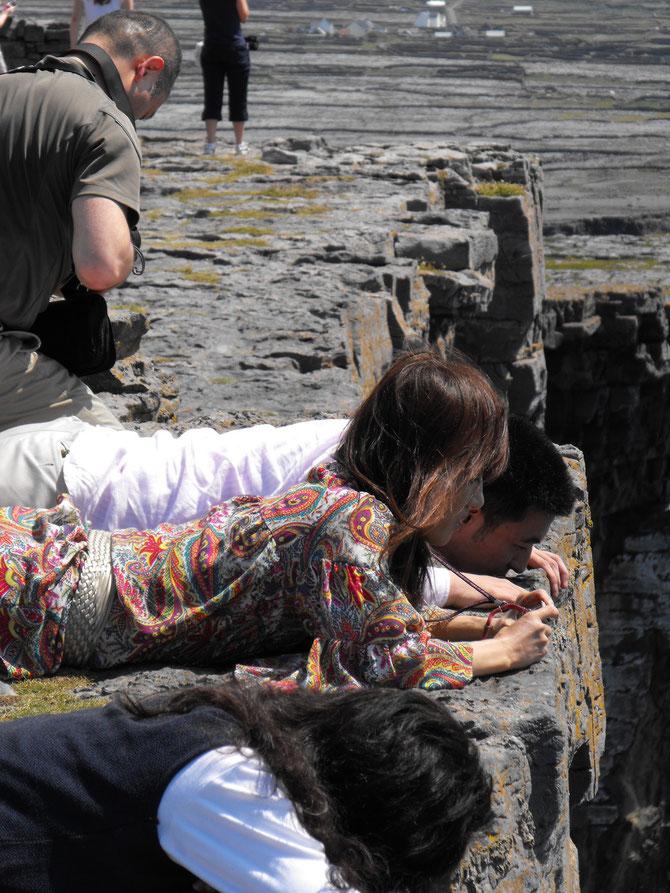 断崖のそばで立つことは、とても危険・腹ばいになって海をの即ツアー参加のみなさん