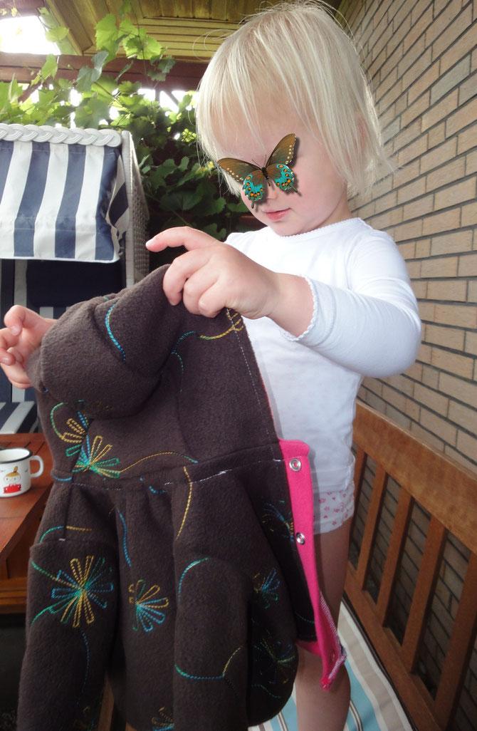 Das Käferchen, als künftige große Schwester, begutachtet kritisch die neue Babyjacke...