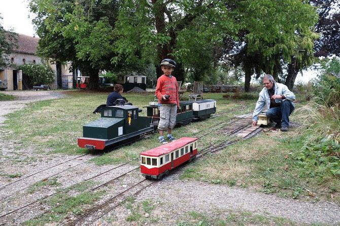 """Août 2012. Train radiocommandé, """"Jarditram"""" et dans le fond automotrice à voie de 60 cm, sillonnent le parc du château."""