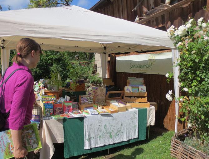 Unser Sonnenwirbel-Stand in Burgstall - eingebettet zwischen weißen Kletterrosen und Trockenmauer.