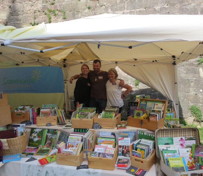 Rosenmesse 3: Das breit grinsende Sonnenwirbel-Verkaufsteam zwischen Natur- und Gartenbüchern.