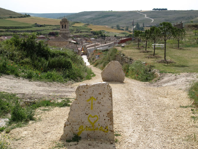Nach über 30 km lange Etappe taucht aus der Senke lang ersehnter Kirchenturm von Hontanas.