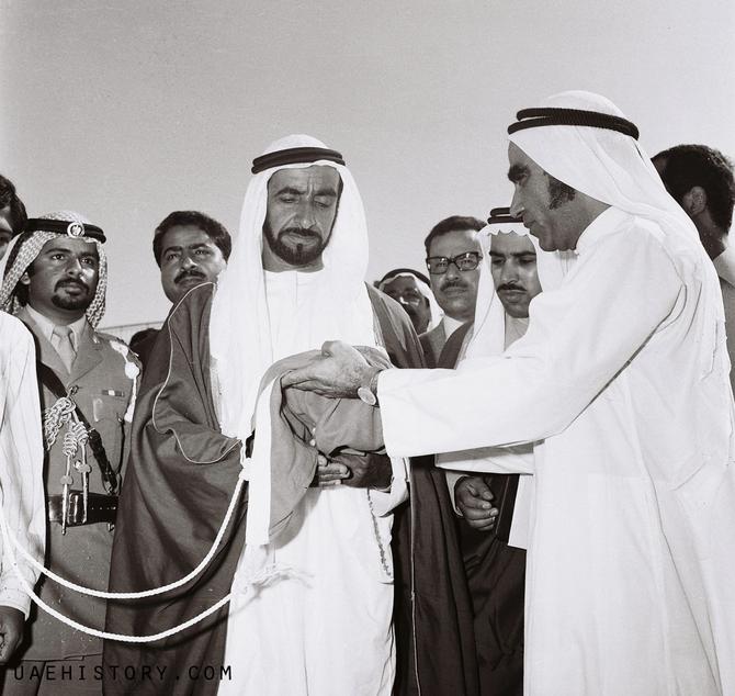 2 DEC. 1971. MAHDI AL TAJIR TEND à L'EMIR ZAYED LE PREMIER DRAPEAU DES EMIRATS.