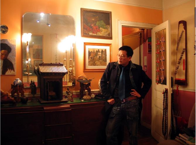 2006. KIM-KHÔI CHEZ LUI ENTOURE DES TABLEAUX DE SON GRAND-PERE NAM SON ET DE SA COLLECTION D'ANTIQUITES D'ASIE.