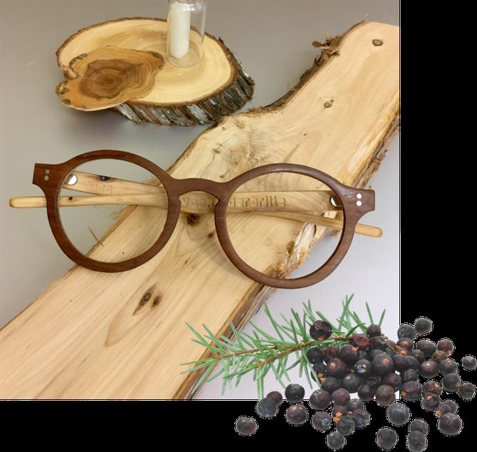 Wacholder-Brille auf Holzbrett und Wacholderbeeren