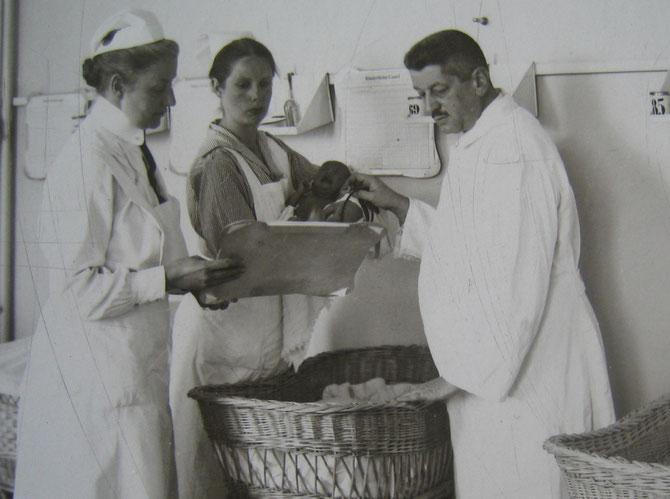 Dr.Felix Blumenfeld mit zwei Krankenschwestern und einem Säugling
