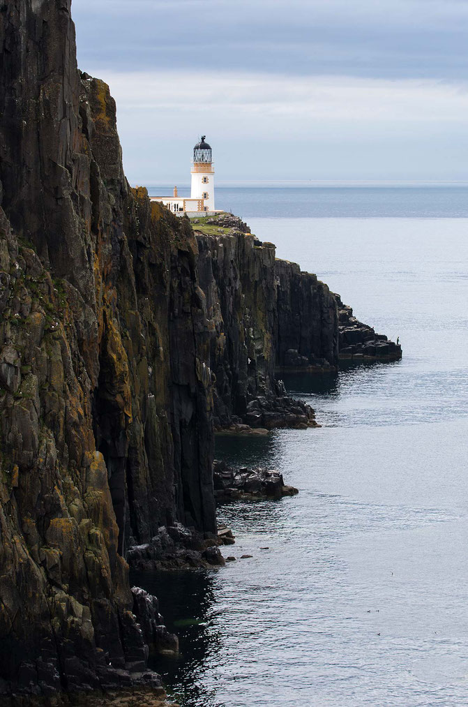 Neist Point Lighthouse on a cliff with ocean and fisherman, upright format, Isle of Skye, Scotland, 12025x1820px