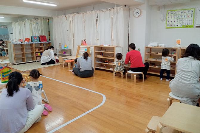 1歳児の親子で学ぶコースでモンテソーリ活動を体験。コップを使ったあけ移しの活動に集中して取り組んでいます。