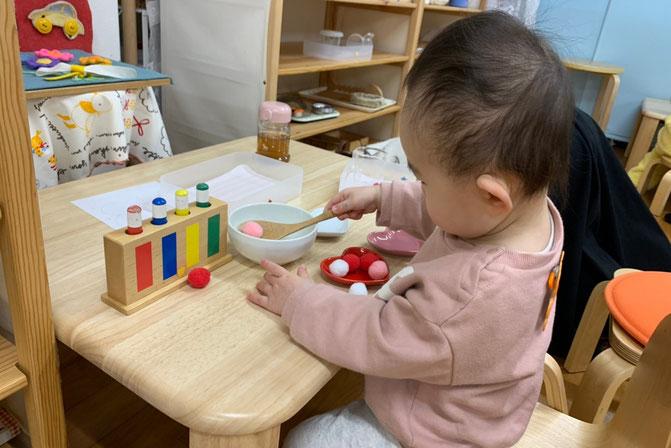 幼児教室のモンテッソーリの個別活動で1歳児が花を生ける活動を行っています。