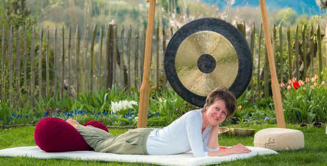 Frau liegt auf Massagematte im Garten vor einem großen Gong