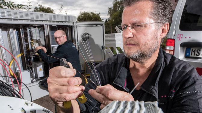 Foto: Telekom (Glasfaser werden beim Spleißen fachmännisch verbunden.)