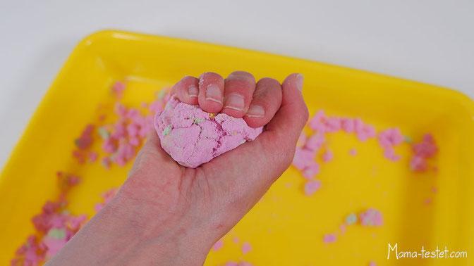 Der Magic Spielsand lässt sich sehr gut kneten. Zerreibt man ihn zwischen den Fingern, fallen kleine und große Krümmel hinunter.