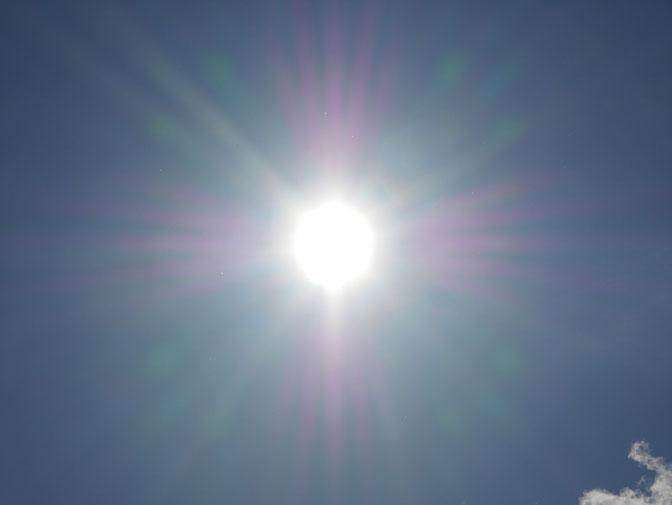strahlende Sonne, blauer Himmel, bunte Lichtstrahlen