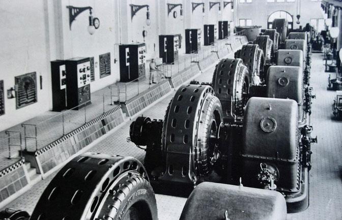 Blick in den damaligen Maschinenraum mit sieben horizontalachsigen Pelton-Turbinen. Das Bild zeigt jeweils das Turbinen(gehäuse) links, den Generator rechts.