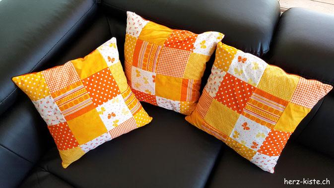 Drei Kissenbezüge mit orangem Patchwork