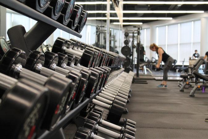 Aufgeräumter Freihantelbereich in einem Fitnessstudio. Im Hintergrund sieht man eine Frau, die trainiert.