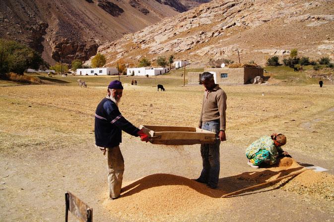 Bewohner aus Pasor bei der manuellen Getreideverarbeitung. Auch dieses Dorf wurde zu 50% zerstört.
