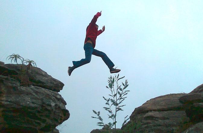 Jemand springt von einem Felsen zum nächsten