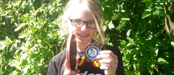 Lisann präsentiert in Ferndorf stolz ihre Medaille von der Bezirksrangliste.