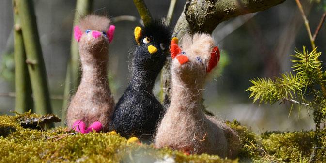 Drei Alpakas aus Filz in verschieden Farben auf einem Baumstamm