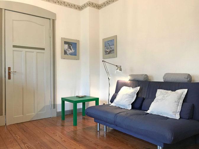 Ferienwohnung Strandkorb: gemütliches Wohnzimmer mit modernem Sofa, Flachbild TV und großzügigen Essbereich