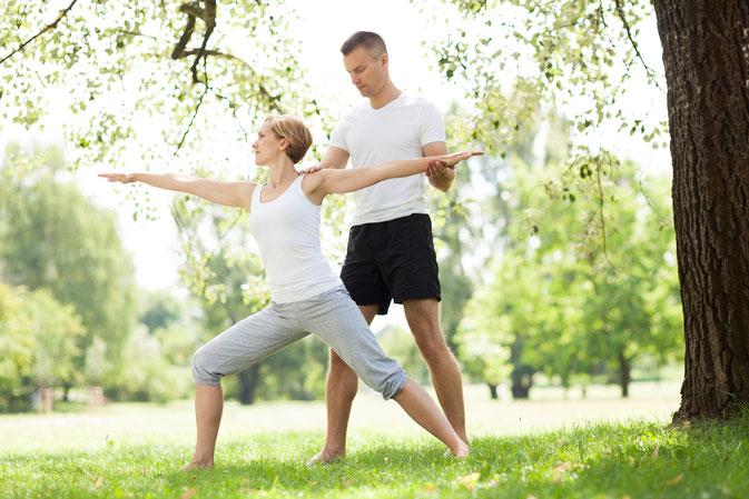 Personal Trainer hilft Yoga-Schülerin in der Kriegerstellung